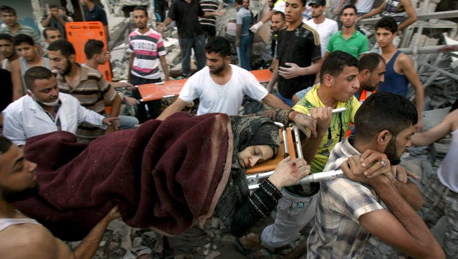 Palestinians evacuate a survivor of an Israeli air strike that hit the Al Ghoul family building in Rafah, southern Gaza Strip, Sunday, Aug. 3, 2014.