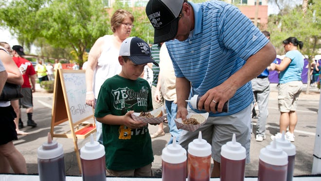 Scott Starmer pours sauce for son Brayden's pulled- pork sandwich from the Scottsdale BBQ Co. at the Great American BBQ & Beer Festival in Chandler.