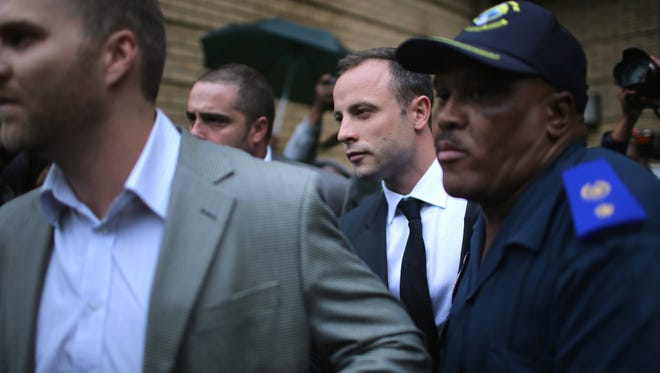 Pistorius leaves court at the end of the first day of his trial.