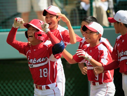 Japan's Takuma Takahashi, left, celebrates after hitting a solo home run against the West Team from Las Vegas.