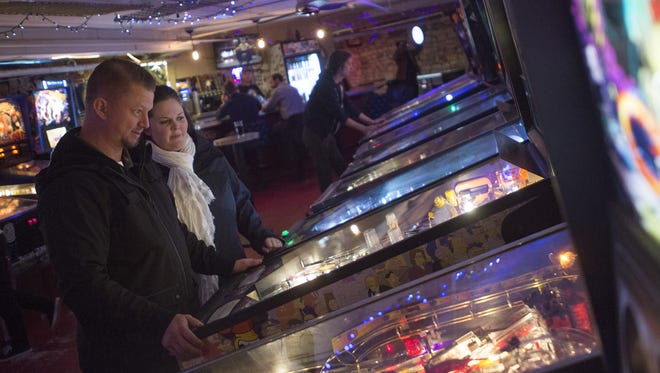 Dan and Emily Morris play on a machine at Pinball Jones in Old Town on Friday, December 8, 2017.
