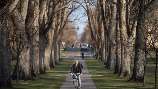 A cyclist makes his way through The Oval at CSU during Winter Bike to Work Day on Wednesday, December 13, 2017. Stations around Fort Collins offered breakfast or bike maintenance to cyclists on their way to work.