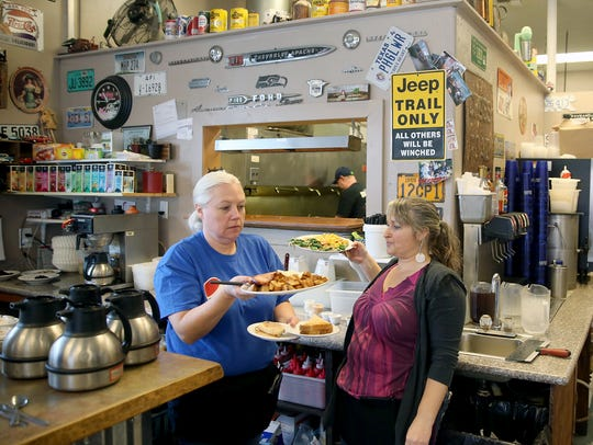 Evalina Kenady, center, co-owner of That One Place in Port Orchard, and server Vonda Wright dodge each other to deliver breakfasts from the kitchen to customers. The restaurant, which opened during the recession, has a large following.