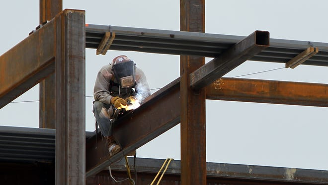 An ironworker welds structural steel as work continues on buildings at Liberty Center, a $350 million mixed-use project scheduled to be up in October.