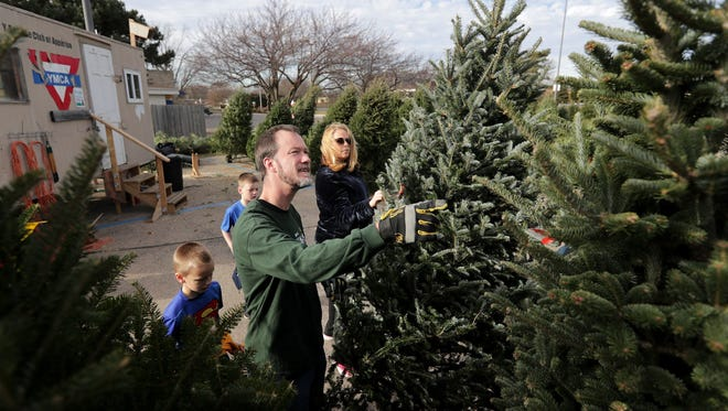 Chris and Sara Birn of Appleton look for a Christmas tree with their sons Nick and Ben at the YMCA Christmas tree lot in the parking lot of Festival Foods on Northland Avenue in Appleton.