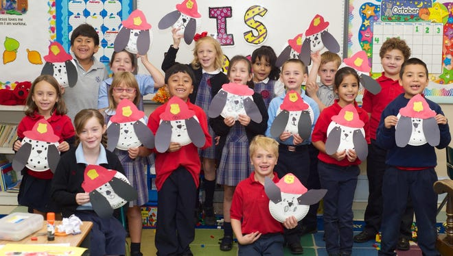 First-grade students at Bishop Schad Regional School in Vineland show off the fire dogs they made after a visit from the Vineland Fire Department.