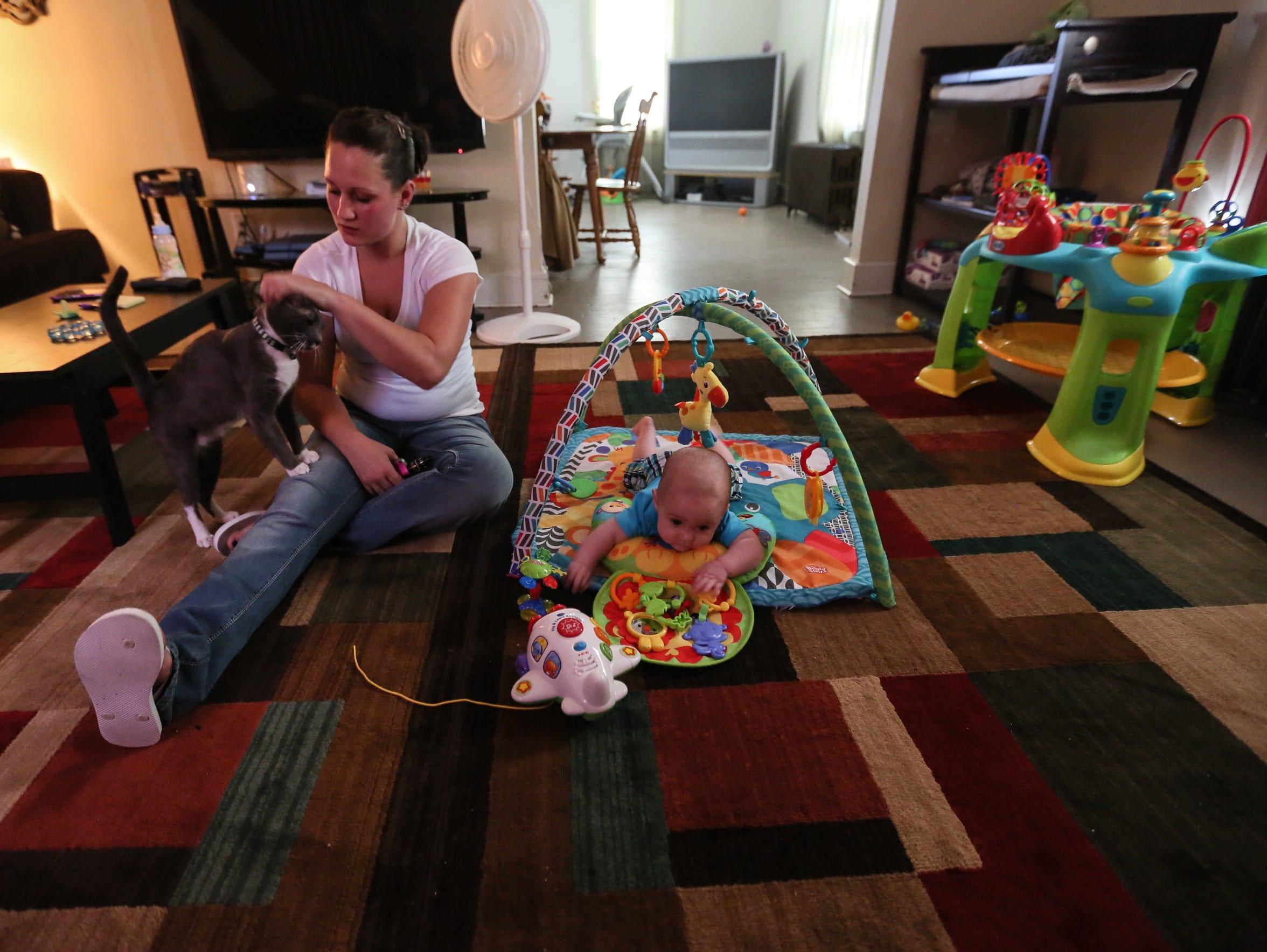 Amanda Lofland, 27, pets the family cat Harley while