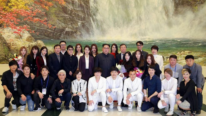 North Korean leader Kim Jong Un (second line center) and his wife, Ri Sol-Ju (second line sixth from left), pose with South Korean musicians after a rare concert at the 1,500-seat East Pyongyang Grand Theatre in Pyongyang on April 1, 2018.