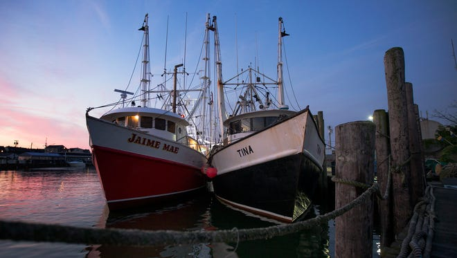 Fishing boats sit docked along Manasquan Inlet in Point Pleasant Beach,