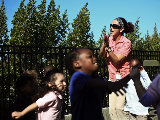 Carmen Starkweather, right, leads a dance and sing a long with children on the playground at Fun Time Early Childhood Academy.