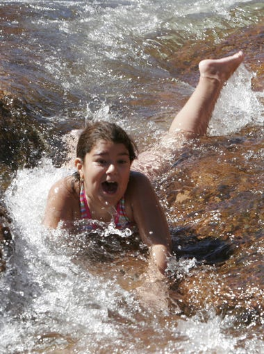 Jailene Silva of Gilbert takes a ride down the slippery rocks  at Slide Rock State Park in Sedona.
