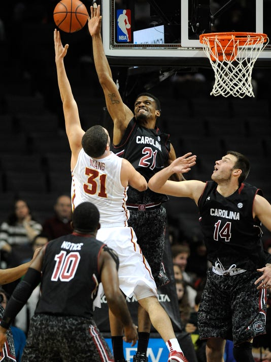 South Carolina's forward/center Demetrius Henry (21) blocks a shot by Iowa State's forward Georges Niang (31) as South Carolina's guard Duane Notice (10) and forward Laimonas Chatkevicius (14) defend during the first half of an NCAA college basketball game at Barclays Center on Saturday, Jan. 3, 2015 in New York. (AP Photo/Kathy Kmonicek)