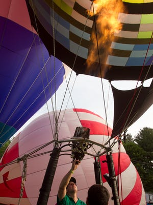 Sullair balloon pilot Shawn Raya keeps his tethered balloon inflated by lighting a torch that heats the air inside Wednesday, June 14, 2017 for the Michigan Challenge Balloonfest media night.