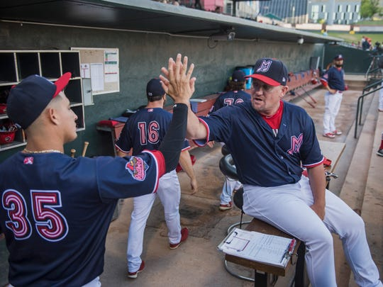 Memphis Redbirds manager Stubby Clapp, right, high-fives pitcher Giovanny Gallegos before a game Aug. 7, 2018 at AutoZone Park.
