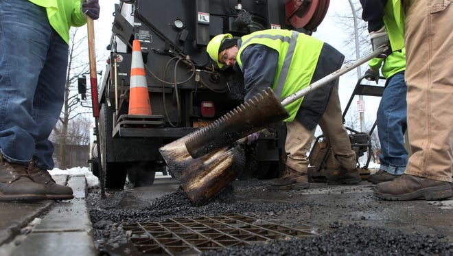 Mike Arcarisi works on patching potholes during city street maintenance. File photo.