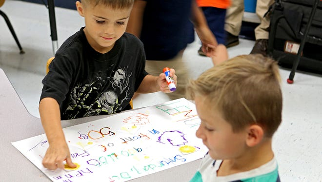 A Fain Elementary kindergartner works on a poster to market the kindergartners' lemonade stand in Emily Vann's classroom Wednesday afternoon.