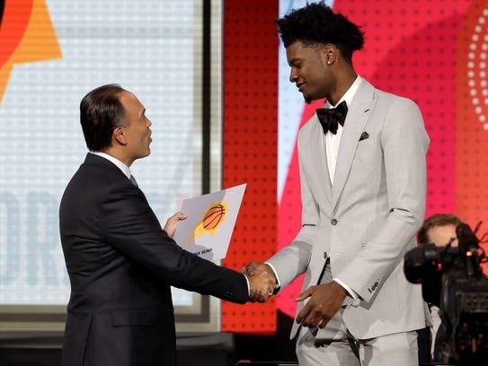 El comisionado de la NBA, Mark Tatum (izq.) felicita