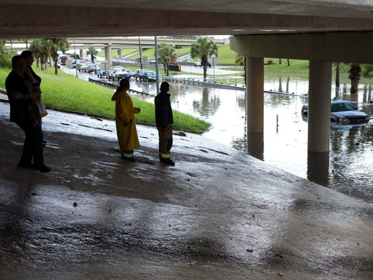 People and firefighters stand underneath an overpass