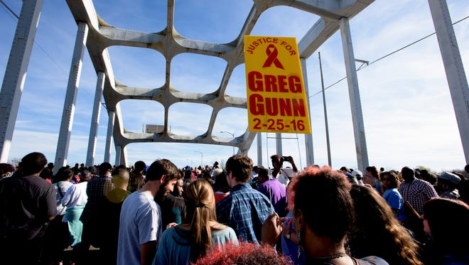 A justice for Greg Gunn sign is carried during the re-enactment of the Bloody Sunday march across the Edmund Pettus Bridge in Selma, Ala. on Sunday March 6, 2016.