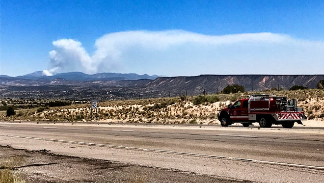 Fire crews head toward the Jemez Mountains along U.S. 550 in Rio Rancho, N.M., as the smoke plume from a prescribed fire grows on Thursday, June 15, 2017. Sandoval County Sheriff's Lt. Keith Elder says deputies were initiating the evacuation of a subdivision along State Highway 4. He was unsure of how many homes were in the area.