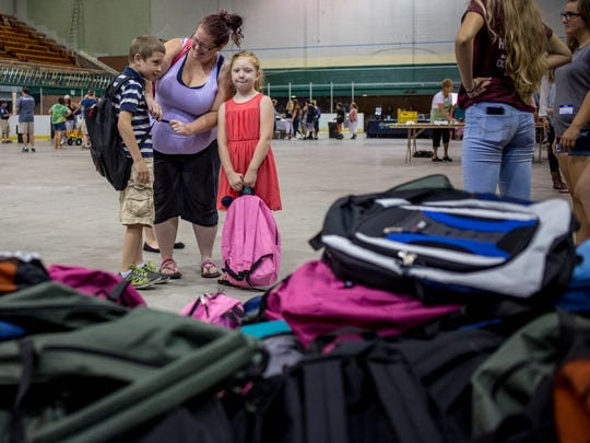 Alena Boyd, of Port Huron, helps her children Luckas Long, 9, and Halie Long, 5, with their backpacks during the annual backpack giveaway hosted by Blue Water Community Action Wednesday, August 17, 2016 at McMorran Arena in Port Huron.