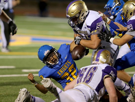 North Kitsap's Connor Westby (top) knocks the ball