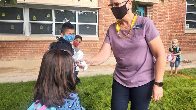 Kindergarten teacher Chris Smith checks the temperature of a student outside the Pueblo School for Arts and Sciences Jones Campus Thursday.