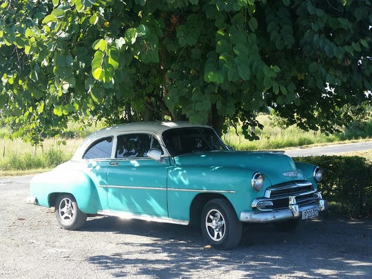A classic car cools down in the shade in Cuba is seen