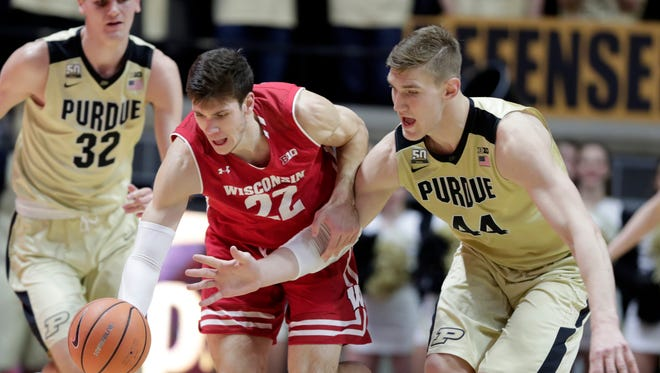 Purdue center Isaac Haas, right, and Wisconsin forward Ethan Happ go after a loose ball in the first half on Tuesday.