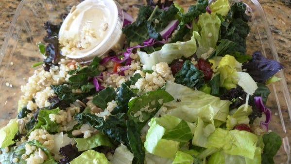 Fresh Organic Restaurant's colorful kale Caesar salad with purple cabbage, quinoa, toasted sunflower seeds, onion and Craisins.