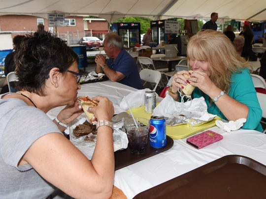 Angela Noto, left, of Pleasant Valley, enjoys a gyro with Chris Lehan, right, of Hyde Park at the annual Greek Festival at Kimisis Greek Orthodox Church in the Town of Poughkeepsie.