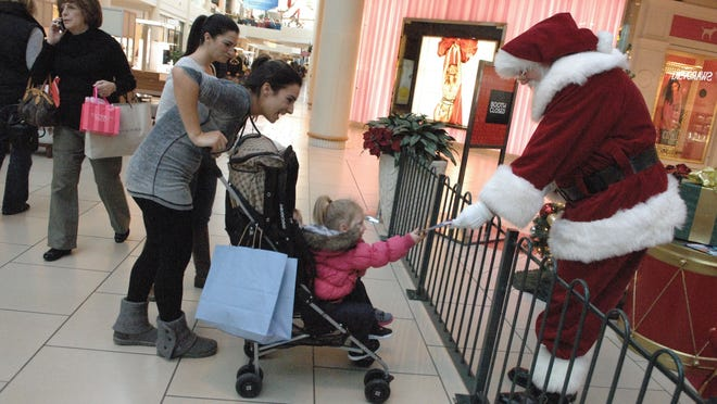 Christmas shoppers Lauren Craven and her 2-year-old daughter Charlotte of Freehold meet with Santa at the Freehold Raceway Mall in Freehold Township.