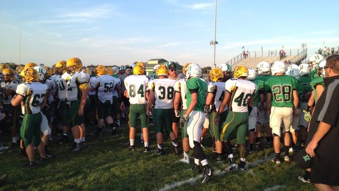 Harrison players walk over to shake hands with Little Miami after a moment of silence before Friday's game.