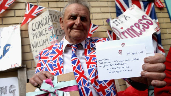 Royalist Terry Hutt poses with a cake and card he recieved from Kensington Palace on his 80th Birthday as waits for new royal baby at St Mary's Hospital in London on April 30.