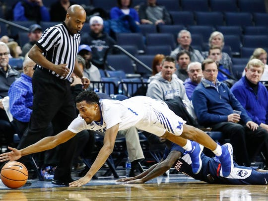 Memphis guard Jeremiah Martin (left) dives for a loose ball against UConn during second half action at the FedExForum in Memphis Tenn., Tuesday, January 16, 2018.