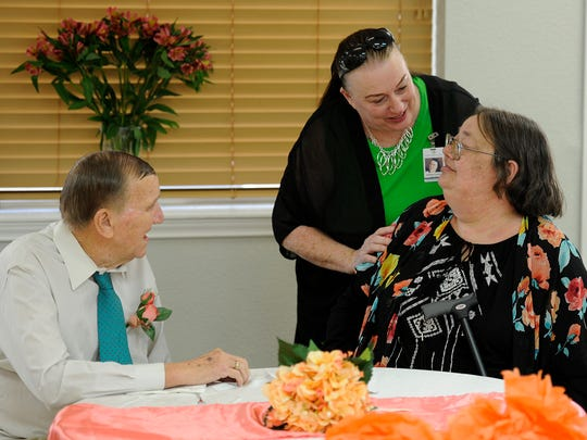 Barbara Lohmann, top right, congratulates Richard Adams and JoEllen Choma during their wedding reception Friday, March 17, 2017, at Northern Oaks Living and Rehabilitation Center.