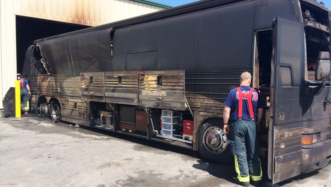Firefighters examine one of two recreational vehicles that were damaged by fire Sunday in Grand Chute.