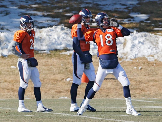 Denver Broncos quarterback Peyton Manning (18) throws a pass at practice for the football team's NFL playoff game against the San Diego Chargers at the Broncos training facility in Englewood, Colo., on Wednesday, Jan. 8, 2014. Backup quarterbacks Zac Dysert (2) and Brock Osweiler (17) watch.
