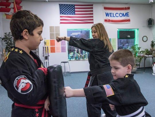 Kelly Perkins shows Mario Popescu, 9, and Thomas Smolarek,