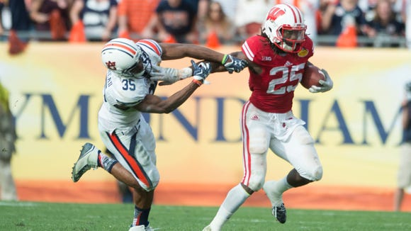 Wisconsin running back Melvin Gordon (25) stiff arms Auburn defensive back Jermaine Whitehead (35) during the Outback Bowl between Auburn and Wisconsin at Raymond James Stadium in Tampa, Fla., on Thursday, Jan. 1, 2015. Wisconsin defeated Auburn 34-31.