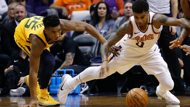 Phoenix Suns forward Marquese Chriss (0) and Utah Jazz guard Donovan Mitchell (45) dive after a loose ball during the first half of an NBA basketball game Friday, Feb. 2, 2018, in Phoenix. (AP Photo/Ross D. Franklin)