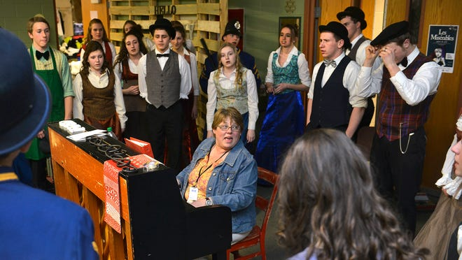 """Holdingford High School teacher Kathleen Waletzko leads """"Hello, Dolly!"""" cast members through a few of the songs before a dress rehearsal Tuesday at the school. Waletzko is retiring after 35 years teaching there."""