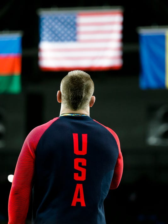 Gold medalist United States' Kyle Frederick Snyder listen to the United Staes' national anthem during the winners ceremony of the men's 97-kg freestyle wrestling competition at the 2016 Summer Olympics in Rio de Janeiro, Brazil, Sunday, Aug. 21, 2016. (AP Photo/Markus Schreiber)