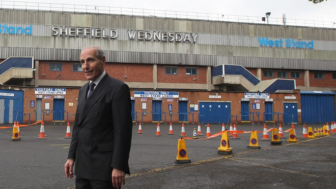HILLSBOROUGH, ENGLAND - MAY 23:  Coroner Lord Justice Goldring (C) stands outside the Hillsborough stadium in Sheffield following a visit by jurors for the inquest into the deaths of 96 Liverpool football fans killed in the Hillsborough disaster on May 23, 2014 in Hillsborough, England. (Photo by Lynne Cameron - WPA  Pool/Getty Images)