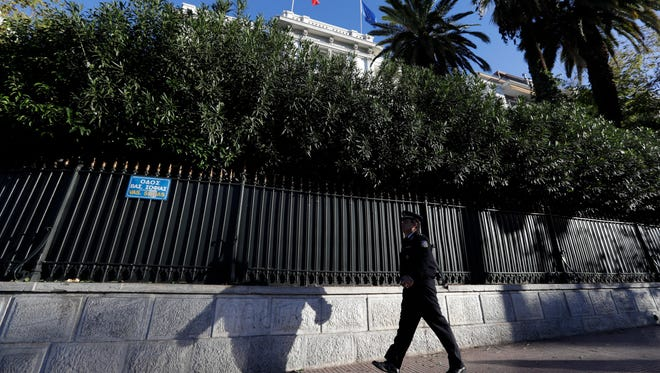 A police officer walks outside the French Embassy in Athens, Thursday, Nov. 10, 2016. Greek police say a hand grenade attack outside the French Embassy in Athens has lightly wounded a policeman.