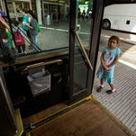 In this photo taken July 4, 8-year-old Gabby, of El Salvador, peaks into a city shuttle bus as she waits for her mother and sister after they and other immigrants and their children were released by U.S. Customs and Border Protection Services at the city bus station in McAllen, Texas. About 90 Hondurans a day cross illegally from Mexico into the U.S. at the Rio Grande near McAllen, according to the Honduran Consulate, and the families are then brought to Central Station in McAllen and each is released on their own recognizance.