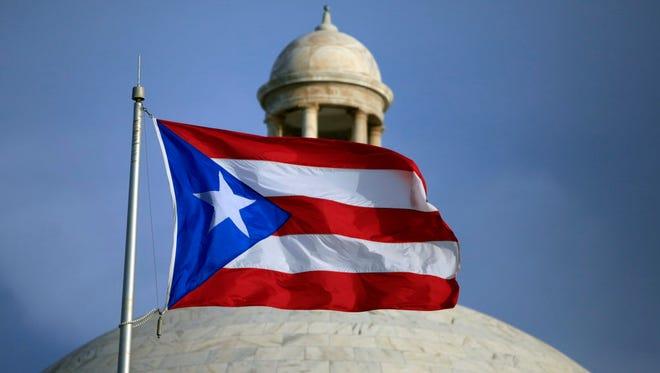 Puerto Rican flag flies in front of Puerto Rico's Capitol in San Juan.