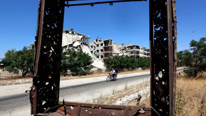 A man rides a motorcycle in Homs, Syria, on Sept. 19.
