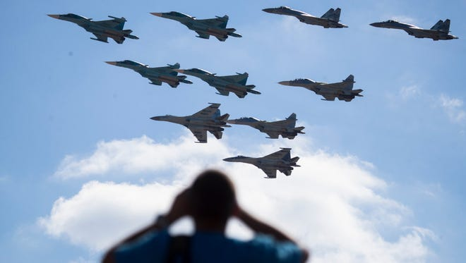 A man watches Russian military jets performing in Alabino, outside Moscow, on Aug. 12.