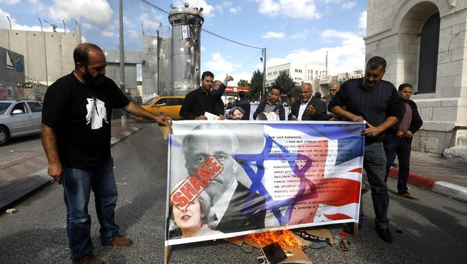 Palestinian protesters burn a banner depicting Arthur Balfour and British and Israeli flags during a protest in the West Bank city of Bethlehem on Nov. 1.